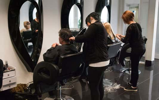 Apprentice hair dressers in salon